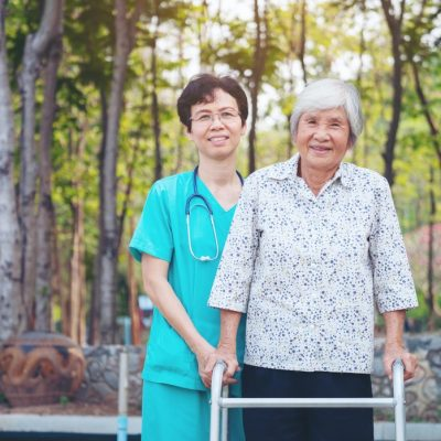 smiling-caregiver-senior-nurse-take-care-a-senior-patient-in-walker-for-relaxing-and-looking-around_t20_ky4pb1